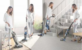 Woman using a cordless vacuum cleaner to clean throughout the home